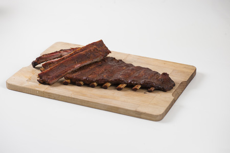 Glazed spare ribs on wooden plate on white background