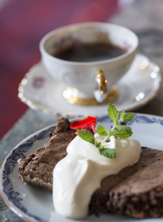 Black coffee and a chocolate cake with whipped cream