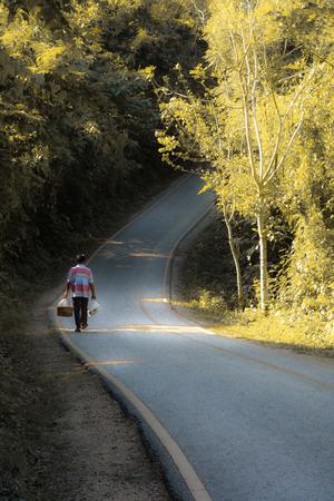 friendless: a man walk alone in a long road Stock Photo