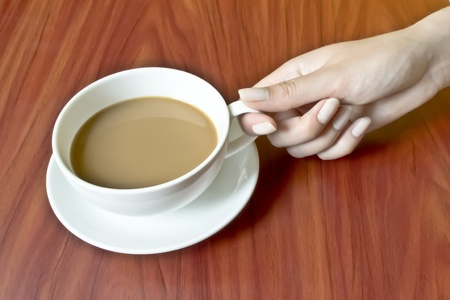 The hands of a young girl holding a cup of coffee photo