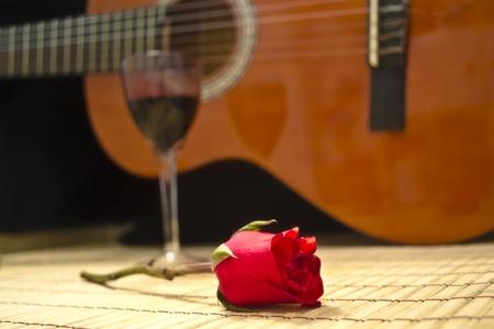 포도 나무의 낭만적 인 저녁 유리는 클래식 기타에게 장미