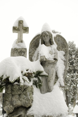 clasped: Close up of a stone angel statue covered with snow Stock Photo