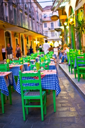 Typical greek taverna with tables outside on the street of Mediterranean Corfu town , street night scenesexy young woman getting out of a swimming pool  photo