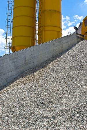 Heaps of granite gravel elimination with yellow silo photo
