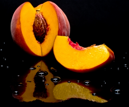 Peaches shot against black and giving a nice reflection with drops of water
