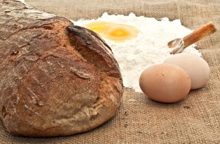 Fresh bread Eggs and flour on the canvas photo