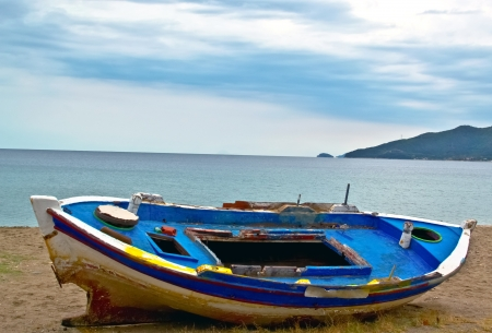 gulls: fishing boat on sand with cloudy blue sky and water Stock Photo