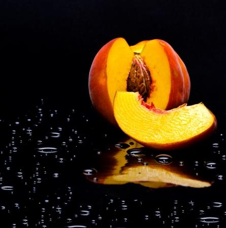 durazno: melocot�n en el fondo negro con gotas de agua Foto de archivo