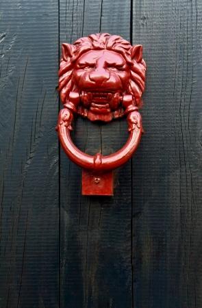 knocker: Close up of an red lion shaped door knocker Stock Photo
