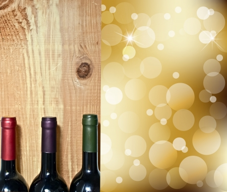 Wine bottle on a wooden table and abstract Lights on gold champagne background photo