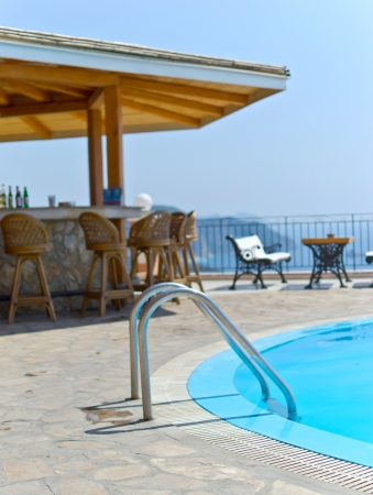 pool bar: Grab bars ladder in the blue outdoor swimming pool with cafe bar
