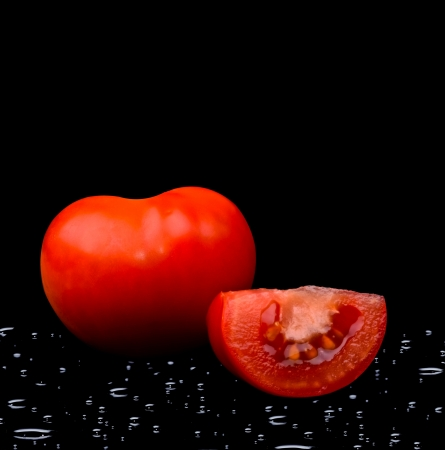Tomato with water drops on black background photo