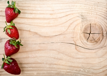 Fresh strawberries on old wooden background photo