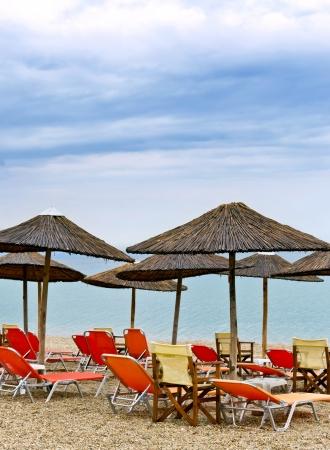 mediteranean: Sun loungers with an umbrella morning on the beach scene Stock Photo