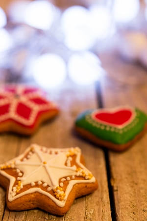 Gingerbread cookies and Christmas decoration over wooden table photo