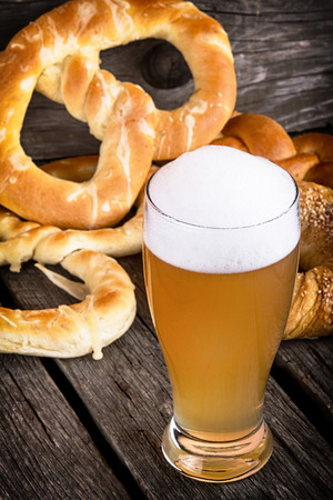 beer with pretzels on wooden table photo