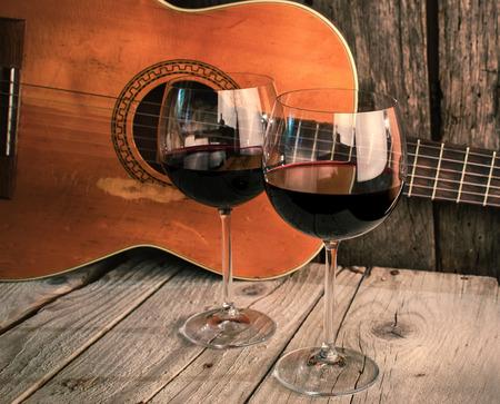 ギターとワインで木製のテーブルのディナー ロマン チックな背景