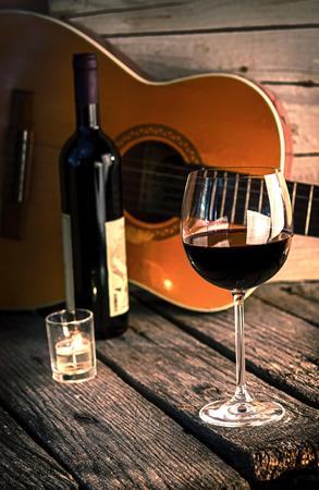 나무 테이블 낭만적 인 저녁 식사 배경에 기타와 와인