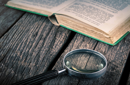 old book and magnifying glass on vintage wood Stock Photo