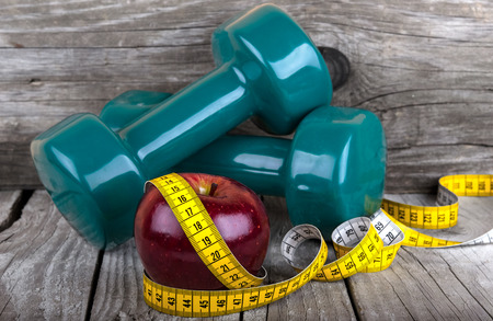 Measuring tape wrapped around a apple weight loss photo Stock Photo