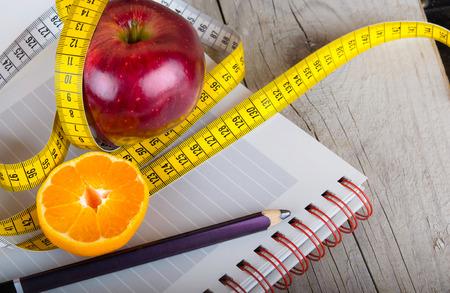 cinta de medir: Cinta métrica envuelto alrededor de una foto de pérdida de peso de la manzana Foto de archivo