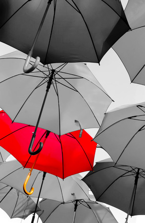 be the identity: red umbrella standing out from the crowd