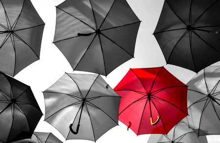 red umbrella standing out from the crowd