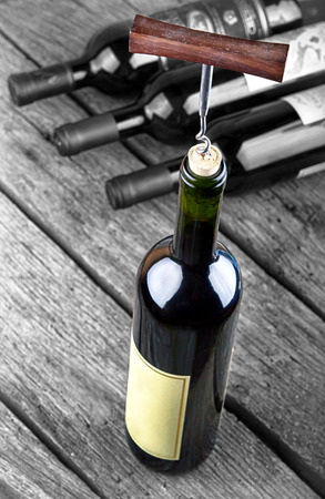 standing out: Wine bottle on a wooden table standing out from the crowd