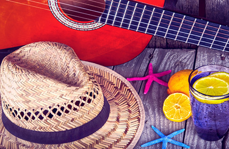 Acoustic guitar hat starfish and glass of tasty fresh lemonade with lemons  on vintage wood summer background Stock Photo