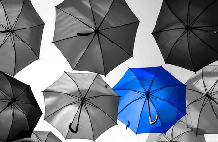 sotto la pioggia: ombrello in piedi fuori dalla folla concetto unico