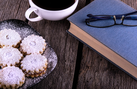 vintage book cup of coffee and gingerbread cookies on grungy wooden background 스톡 콘텐츠