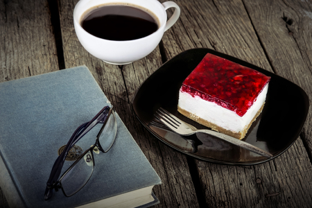 vintage book reading cup of coffee and cheese cake on grungy wooden background