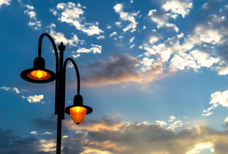 glowing street lamp and blue twilight sky with clouds 스톡 콘텐츠