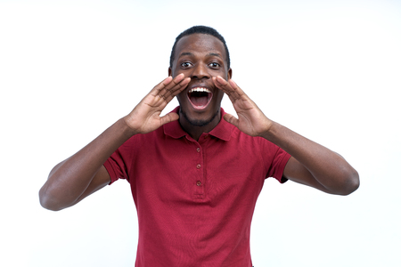 positive young black guy, student, worker employee screams mouth wide open and putting his hands to his face as mouthpiece. Portrait on white background in casual clothing.