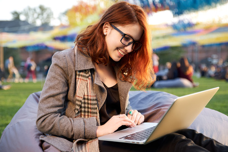 attractive young red-haired woman in glasses with a laptop sits in an autumn park during sunset