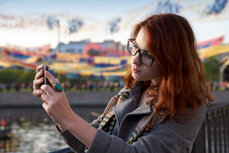 soltería: attractive red-haired girl with glasses in the coat takes on the mobile phone while walking in the Park or an evening at the fair