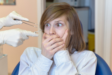 a young woman is shocked by the fear and horror of dental instruments that she looks at with her eyes wide open. The concept of fear of the dentist and dental treatment