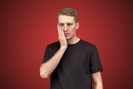 Young attractive male fellow holds palm at the cheek with a disturbed expression, or a nagging toothache. The concept of disorder, the health of the mouth, toothache, slaps.