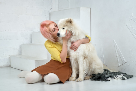 Young girl kissing and hugging a large white friend dog Samoyed. The girl is happy that the dog learned a few training and commands, very intelligent and obedient when trained. coziness and warmth. Stock Photo