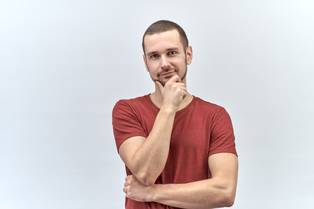 a young man in a red shirt with short hair poses for a portrait on a white background with a wistful dreamy expression looking at the camera