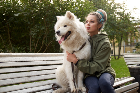 An attractive young woman with dreadlocks sits on a Park bench with her snow-white Samoyed dog. Mistress lovingly embraces her pet and presses him to her. Stockfoto