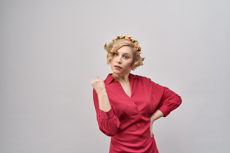 young beautiful blond woman in red dress with evil, serious , threatening expression shows her fist and threatens trouble. An annoyed expression. The concept of education, warning, admonition Stock fotó