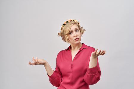 close-up portrait in Studio on white background confused disturbed young girl in a red dress separating hands in front of her in confusion, doubt, protest. Blond hair and wreath of flowers on her head Imagens