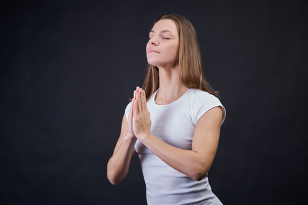 Ordinary blonde woman in white plain t-shirt on isolated black background holding hands in prayer and closed eyes. The girl of European nationality concentrates and learns emotional balance.