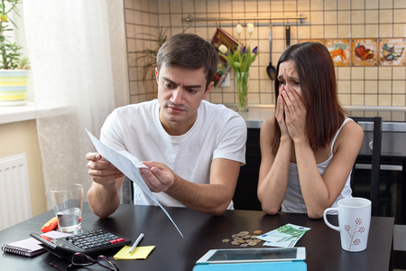 young couple sits at a table in the kitchen and is engaged in the calculation of the home budget, financial assets. A man with serious face holds the document, and his wife cries, and cover her face