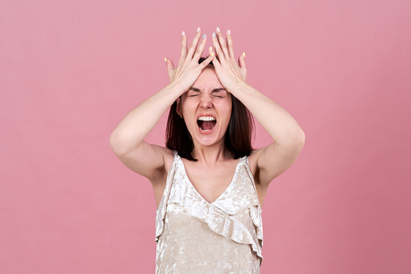 young brunette woman in a rage screams, opening her mouth wide and pressing her palms to her forehead. The concept of anger, negativity, ferocity, failure.