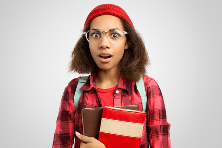 Overjoyed hipster woman looks with amazement, wears big spectacles, carries notepad, exclaims emotionally, stands over white wall with blank space for your information.