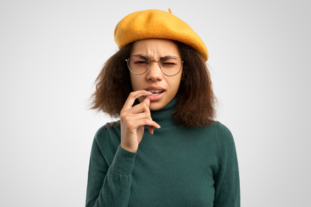 Indoor shot of pensive young female in green polo neck sweater, beret and round spectacles looks thoughtfully in camera. Stockfoto