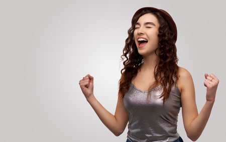 European girl feeling ecstatic, raising fists in celebration, triumph and excitement after she hit the jackpot. Isolated over white studio wall, free space on left side for your promotion or advert. Imagens