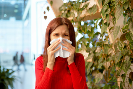 attractive woman, frowning and blowing her nose in a handkerchief. the concept of spring colds and allergies. portrait on the background of the business center and greenery.
